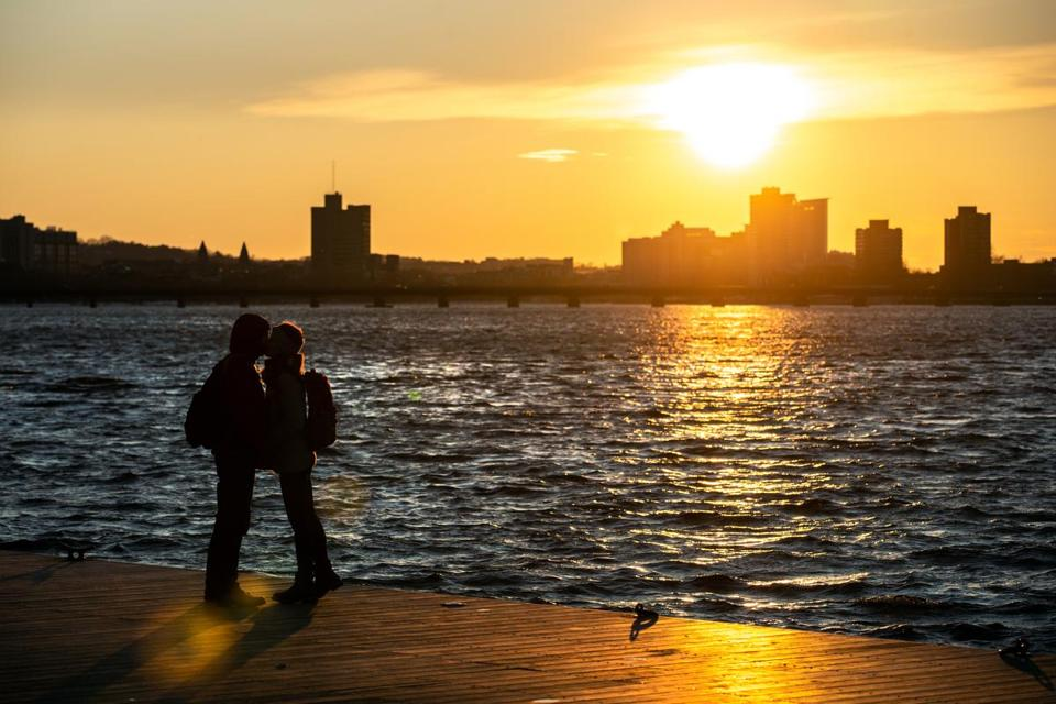 03/11/2019 BOSTON, MA Hamit Sahin (cq) (left) kisses his wife Laura Chambre (cq) of Boston, during the last hour of sunlight on the Charles River Esplanade in Boston. (Aram Boghosian for The Boston Globe)