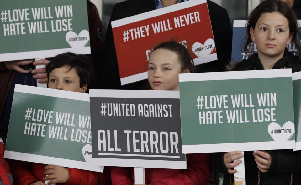 Young demonstrators held banners from the multi-faith group 'Turn to Love' during a vigil at New Zealand House in London.
