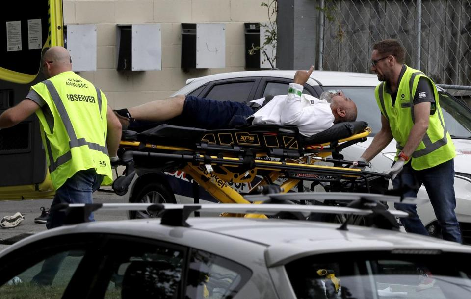 First responders carried a victim away from a Christchurch New Zealand mosque after Friday's shooting