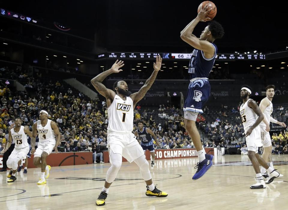 Jeff Dowtin (11) shoots over VCU's Mike'L Simms (1) during URI's Atlantic 10 quarterfinal win in New York.