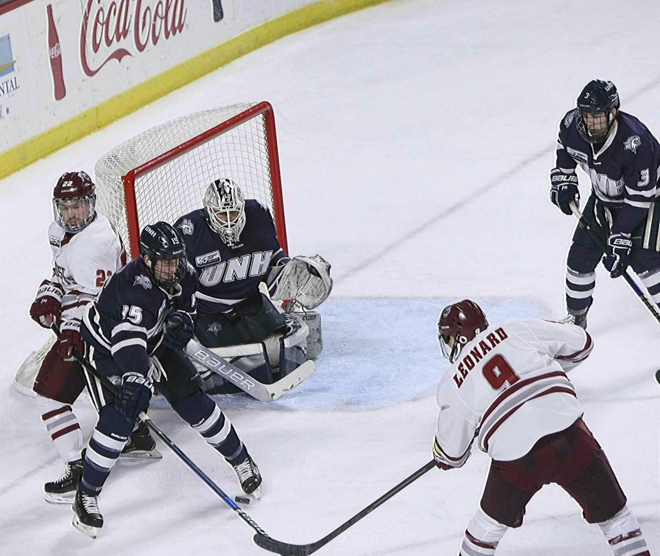 Massachusetts' John Leonard, fires a shot on goal between the skates New Hampshire's Richard Boyd (15) during the first period of an NCAA college hockey game, Friday, March 15, 2019, in Amherst, Mass. (J. Anthony Roberts/The Republican via AP)