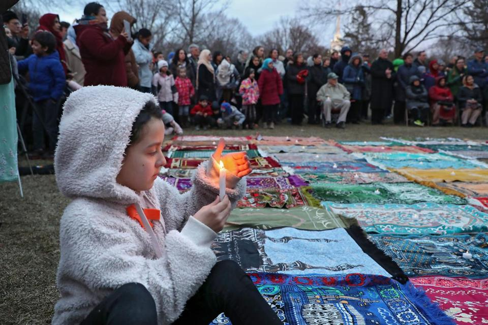 Esma, who chose to give her first name only, held a candle near the 50 symbolic prayer rugs representing the victims of the mosque killings in New Zealand at an interfaith vigil in Lexington.