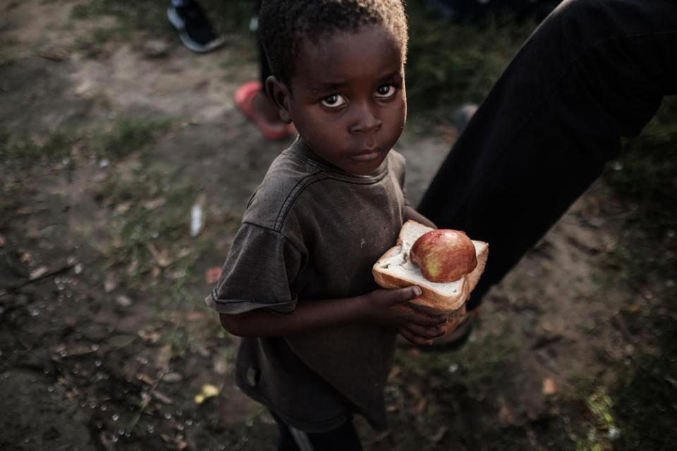 A boy walks after receiving food destribution from a local supermarket at an evacuation center in Dondo, about 35km north from Beira, Mozambique, on March 27, 2019. - Five cases of cholera have been confirmed in Mozambique following the cyclone that ravaged the country killing at least 468 people, a government health official said on March 27, 2019. Cyclone Idai smashed into Mozambique on March 15, unleashing hurricane-force winds and heavy rains that flooded much of the centre of the poor southern African country and then battered eastern Zimbabwe and Malawi. (Photo by Yasuyoshi CHIBA / AFP)YASUYOSHI CHIBA/AFP/Getty Images
