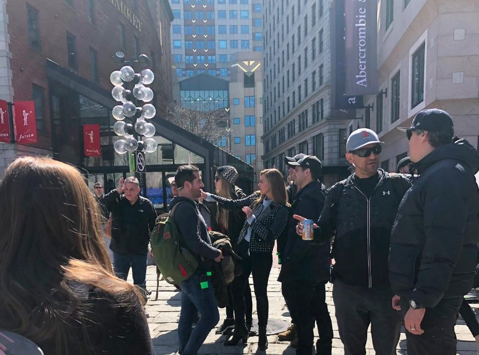 "Hannah Brown (center, in blue) films ""The Bachelorette"" outside of Quincy Market on March 28, 2019."