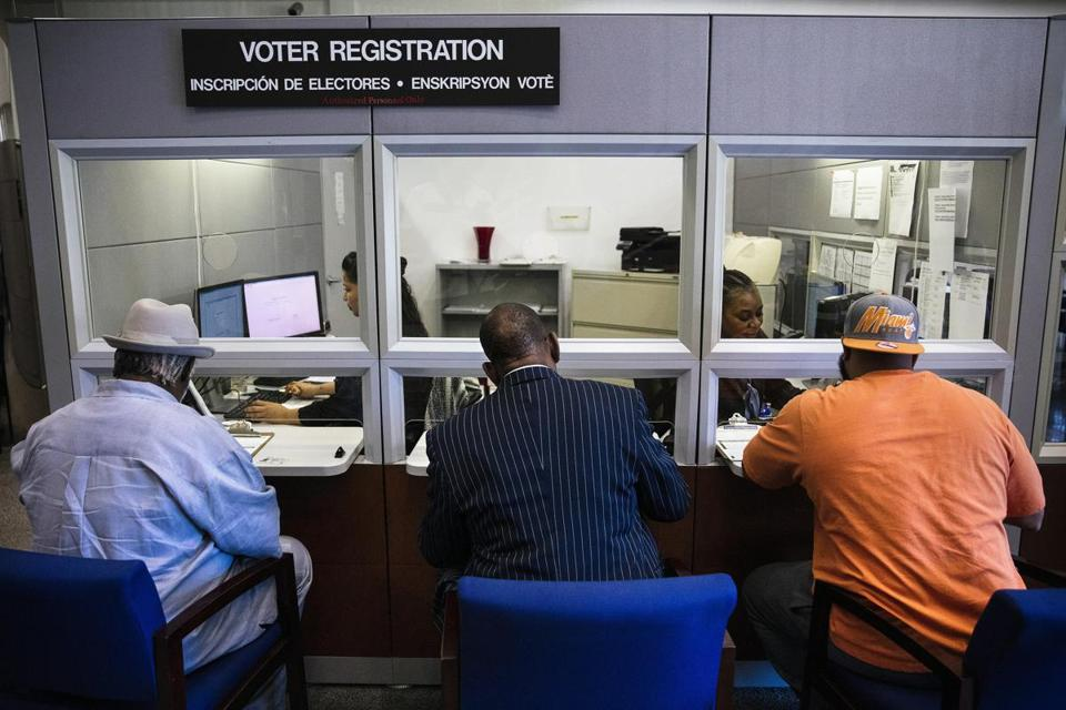 From left, Lorenzo Latson Sr., Clarence Office Jr. and Jerry Armstrong complete their voter registration at the Miami-Dade County Elections Department in Doral, Fla., on Tuesday, Jan. 8, 2019. A historic amendment to the Florida Constitution restoring the voting rights of former felons went into effect on Tuesday. (Scott McIntyre/The New York Times)