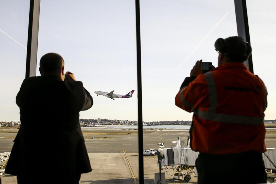 Boston, MA--04/05/2019--Employees at Logan Airport take photos on their phones of the first direct flight from Logan to Honolulu on Hawaiian Airlines Friday morning. (Nathan Klima for The Boston Globe) Topic: 06HawaiianPhoto Reporter:
