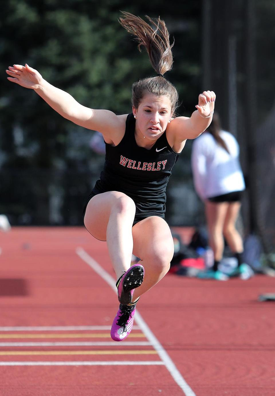 Wellesley's Charlotte Freniere competing in the long jump.