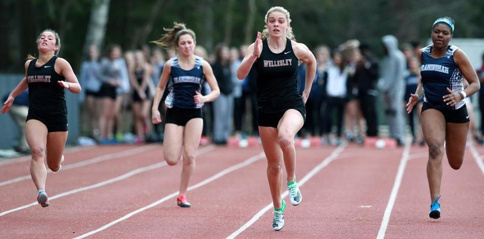 4-10-19: Wellesley, MA: Wellesley High School girl's track team member Abby Comella (second from right) is pictured on her way to winning a heat in the 100 meter dash during a meet vs. Framingham. (Jim Davis /Globe Staff).