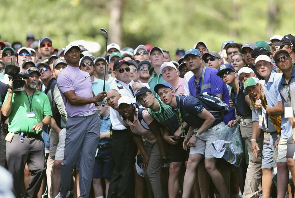 Tiger Woods hits from the gallery along the 11th fairway during the third round of the Masters golf tournament Saturday, April 13, 2019, at Augusta National in Augusta, Ga. (Curtis Compton/Atlanta Journal-Constitution via AP)