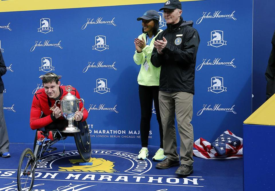 Daniel Romanchuk, of Urbana, Ill., holds the trophy after winning the men's handcycle division of the 123rd Boston Marathon on Monday, April 15, 2019, in Boston. (AP Photo/Winslow Townson)