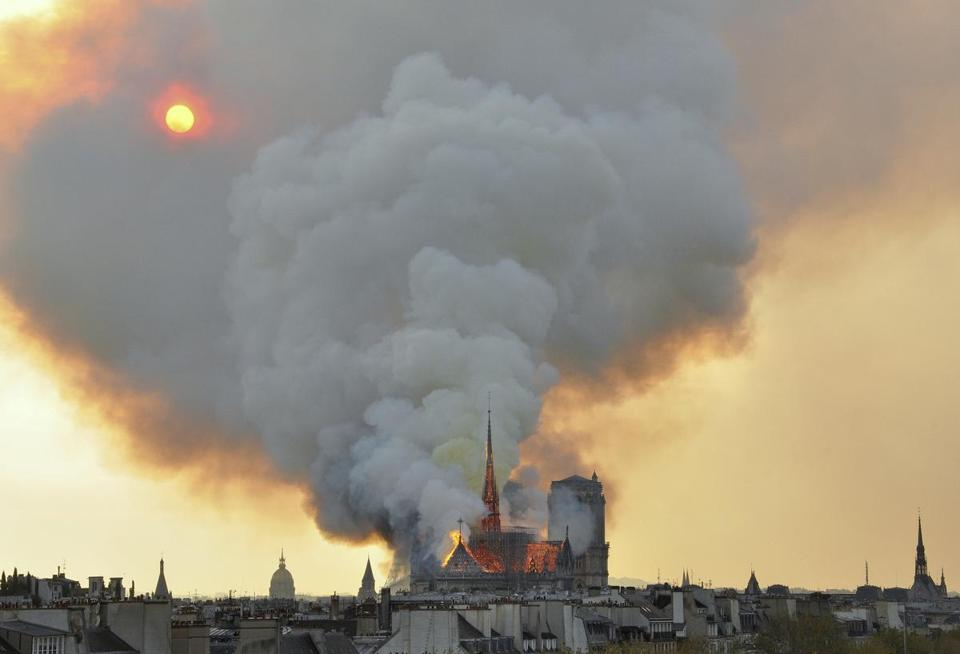 Fames and smoke rose from the blaze at Notre Dame on Monday.