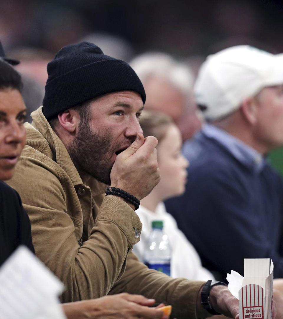 New England Patriots wide receiver Julian Edelman eats popcorn in the front row while watching the second quarter of Game 2 of an NBA basketball first-round playoff series between the Boston Celtics and Indiana Pacers, Wednesday, April 17, 2019, in Boston. (AP Photo/Charles Krupa)