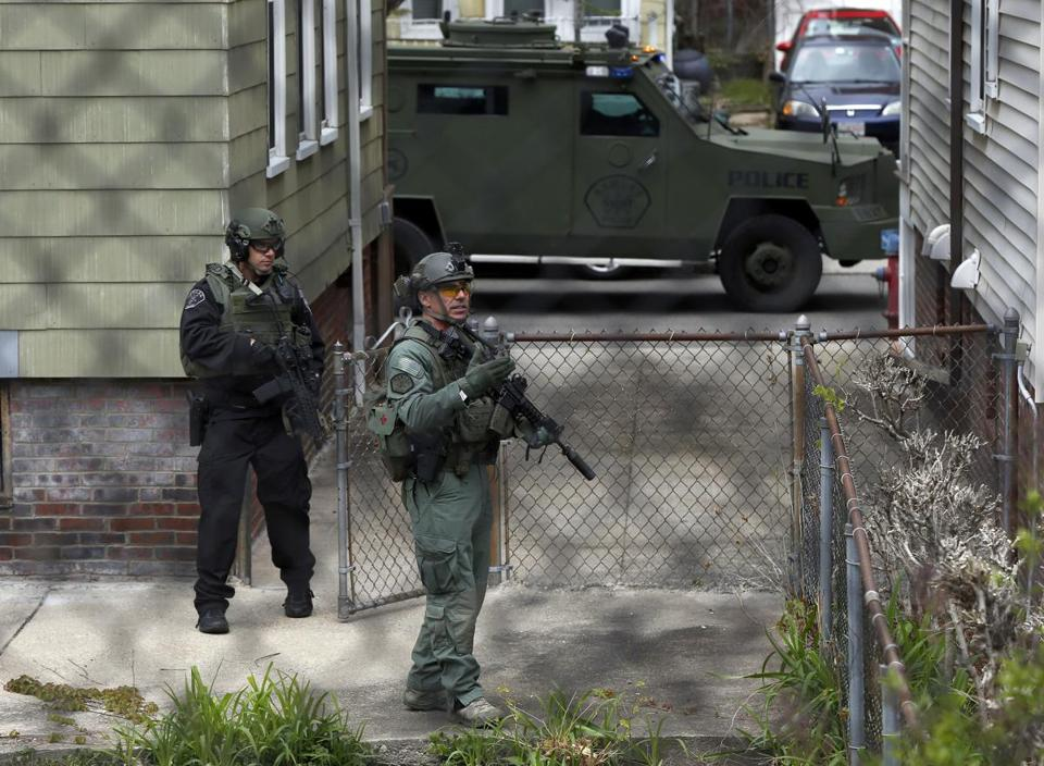 Police officers search a backyard in the Davis Square neighborhood after someone fired a weapon at officers responding to a bank robbery Wednesday, May 1, 2019, in Somerville, Mass. (AP Photo/Michael Dwyer)