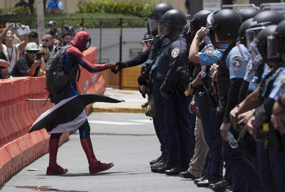 A protester dressed as Spiderman exercises civil disobedience when crossing the perimeter established by the police during a protest against the Federal Fiscal Control Board, as part of the May Day celebration, in San Juan, Puerto Rico, Wednesday, May 1, 2019. The U.S. Congress established the appointed Fiscal Control Board to oversee the debt restructuring in order to combat the Puerto Rican government-debt crisis. (AP Photo/Carlos Giusti)