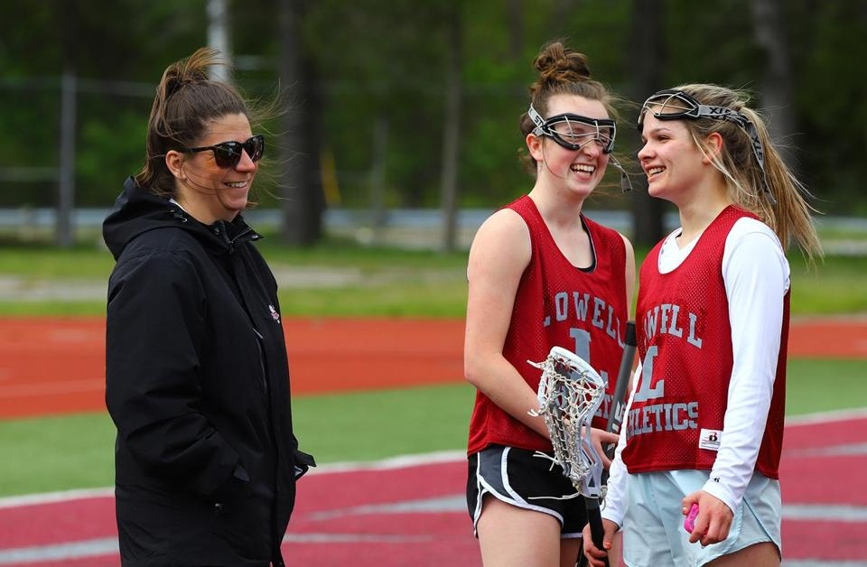 "Lowell coach Kerry Bomil, sharing a word with senior captains Hannah Erickson (center) and Hannah McAnespie (right) during practice, says her team is undaunted. ""They're not looking at the jerseys of the other teams and getting intimidated,"" she said."