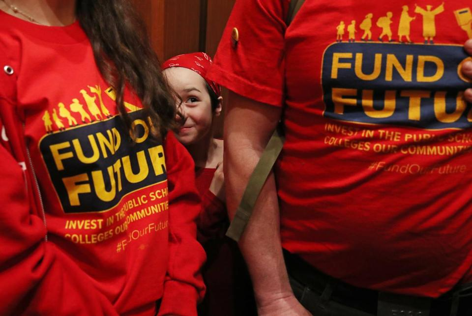 BOSTON, MA - May 16, 2019: Maeve Stern, 9, of Westfield, peaks through her family while riding an elevator during the Fund Our Future Day of Action at the Massachusetts State House in Boston on May 16, 2019. The family was visiting legislators to ask them to pass the Promise and Cherish Acts to reinvest in public education. (The Day of Action to Highlight Urgent Need for Major Reinvestment in Public Schools, Colleges, and Universities) (Craig F. Walker/Globe Staff) section: metro reporter: