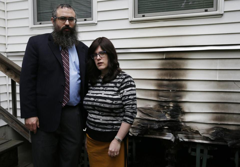 Rabbi Mendy Krinsky (left) and his wife, Chanie, of the Chabad Jewish Center in Needham posed for a portrait beside the spot where someone tried to set their Chabad house on fire.