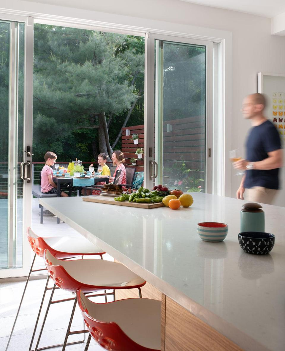 When the weather allows, the family eats dinner on the deck, and the sliding doors remain open. The kitchen countertop is Caesarstone, and the stools are by Calligaris.