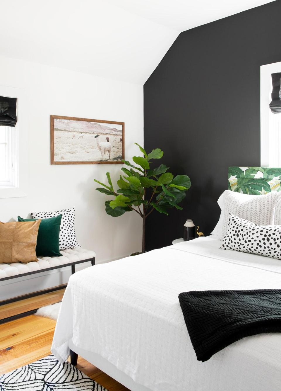 The headboard, upholstered in a tropical leaf print, pops against the black accent wall in one of the home's two guest bedrooms. The llama print is from World Market.