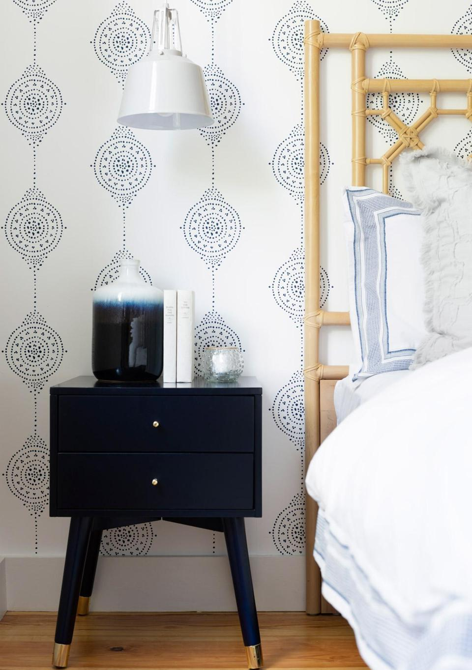"The starting points for the master bedroom were the Luna Stripe wallpaper from Serena & Lily and the rattan headboard. ""I wanted it to be light and neutral, with just a little color,"" Desiree Burns says."