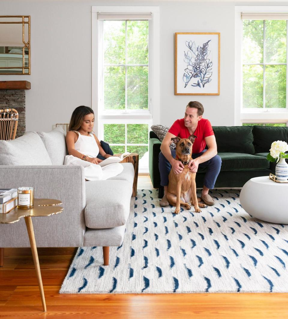 Desiree and Christian Burns and their Lab-mix rescue dog, Sloane, in the living room of their Newport getaway, which they purchased in the spring of 2017.