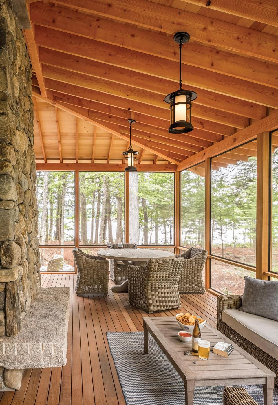 The hand-split granite ledge encircling the chimney supplements the seating on the screened porch. Black lantern-style pendant lights add to the cabin feel.