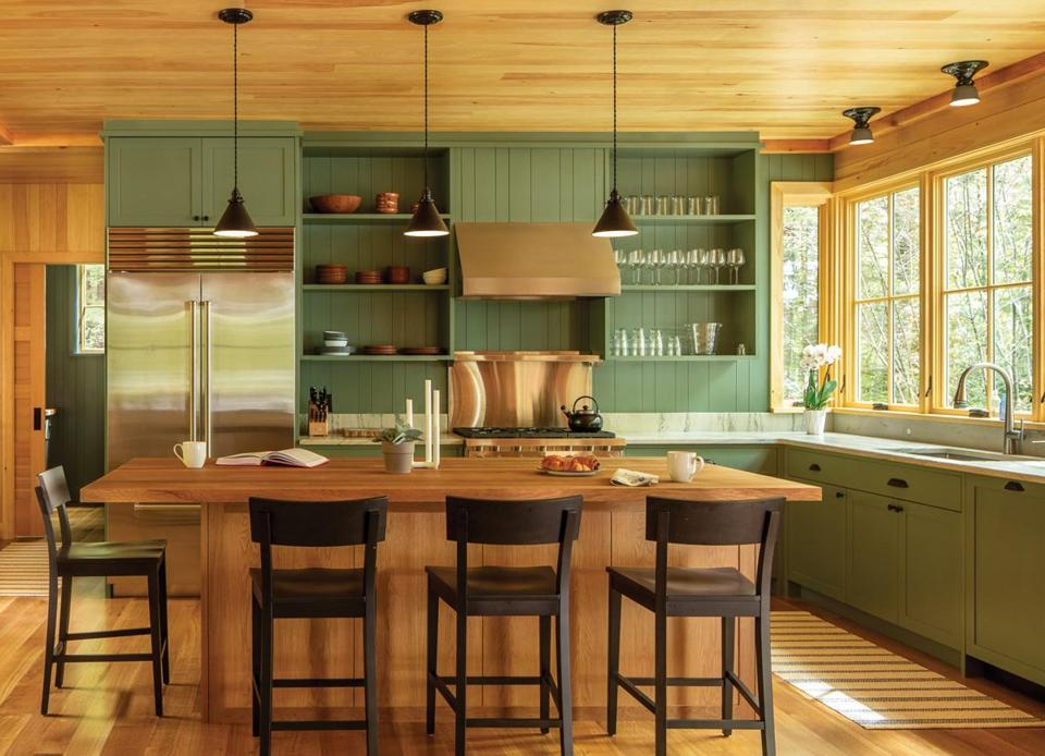 "Designer Krista Stokes chose Farrow & Ball Green Smoke paint for the kitchen cabinetry. ""It was only after the clients approved it that we realized that it's similar to the color of the husband's parents' kitchen next door,""  she says."