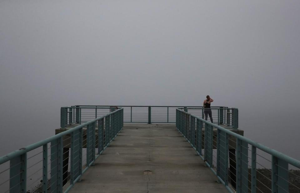 BOSTON, MA - June 19, 2019: Mary Tamul of Quincy looks at the fog on Old Harbor from a pier at Carson Beach in Boston, MA on June 19, 2019. (Craig F. Walker/Globe Staff) section: metro reporter: