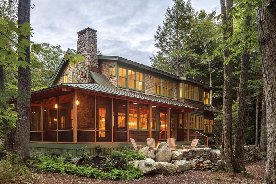 White cedar shingles cover the upper portion of the home's exterior, and red cedar boards run horizontally around the first floor. Low walls built from stones gathered on the site surround the bluestone patio at the back of the house.