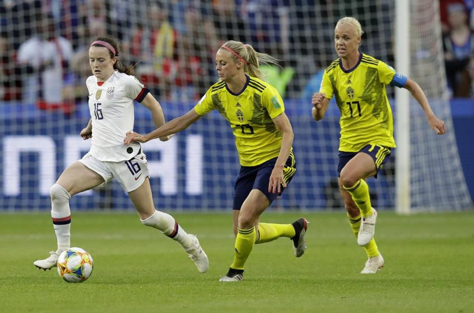 Lavelle (left) takes the ball away from Sweden's Amanda Ilestedt and Caroline Seger.