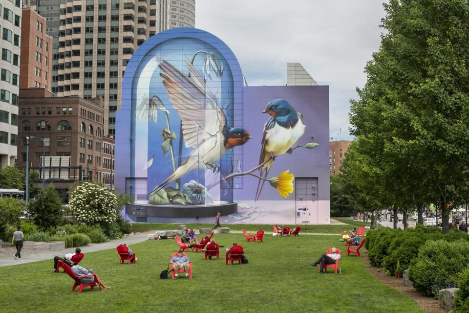 "People lounging on the lawn of the Rose Fitzgerald Kennedy Greenway in front of the mural ""Resonance,"" by the Dutch artist known as Super A (Stefan Thelen)."