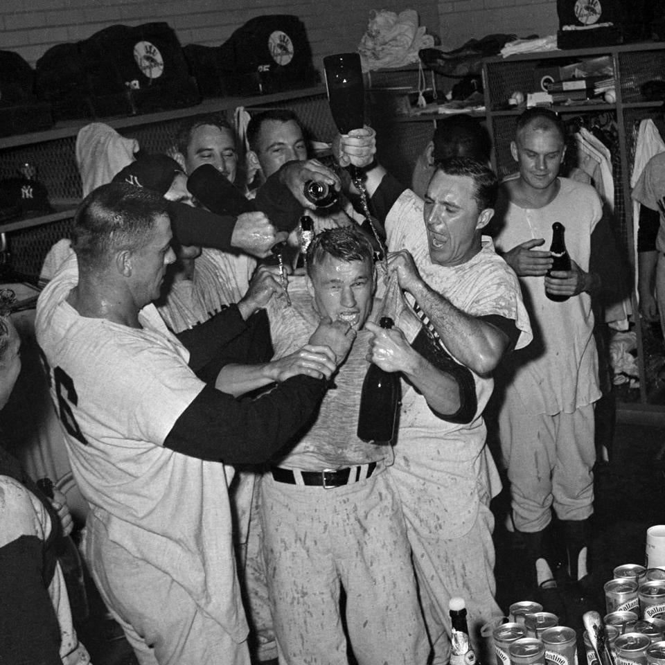 Stars of the New York Yankees celebrated with champagne and horseplay in Minneapolis-St. Paul, Minn,, Sept. 13, 1963 after defeating the Minnesota Twins 2-0 to clinch the American League pennant. Jim Bouton, who pitched his 20th victory, gets the dousing, center, from coach Dale Long, left, and home run-hitting Johnny Blanchard in the clubhouse. (AP Photo/Gene Herrick)