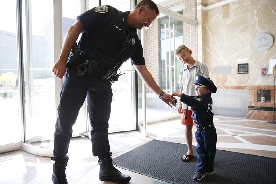 Grant Baker of Cambridge, a toddler who wants to be a police officer when he grows up, visited the Cambridge police station. Officer Mark Smith jokingly handed Grant the keys to his cruiser.