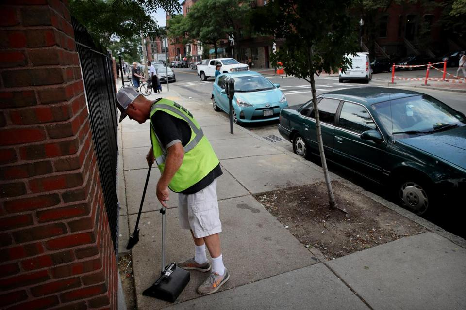 BOSTON, MA - AUGUST 07, 2019: A Boston City employee sweeps up a syringe while cleaning Harrison Ave in front of Boston Medical Center and across from Worcester Square Boston, MA on August 07, 2019. (Tensions over an influx of drug users and homeless people into new areas -- including the South End -- beyond the area known as the methadone mile.) (Craig F. Walker/Globe Staff) section: Metro reporter: