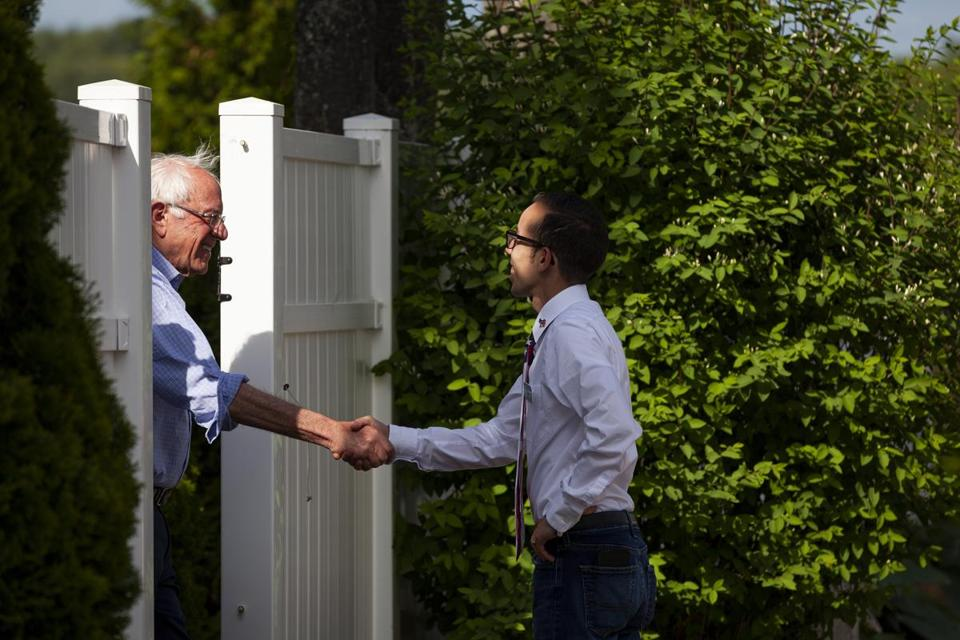 Carlos Cardona greets Bernie Sanders before Sanders speaks to guests at Cardona's house in May. MUST CREDIT: Photo for The Washington Post by Elizabeth Frantz