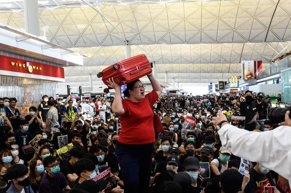 A traveller shouted while holding her luggage as she tried to enter the departures gate area as Hong Kong pro-democracy protesters blocked access during another demonstration at Hong Kong's international airport on Tuesday.