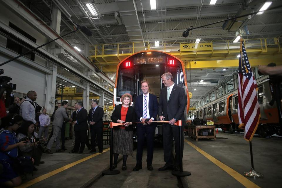 Stephanie Pollack, Steve Poftak, and Charlie Baker cut a ribbon in front of a new Orange Line train.