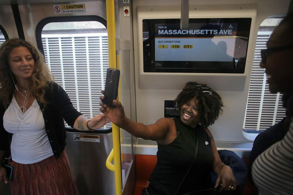 Seated under a new information screen, Roxbury resident Antoinette Carter rejoiced as she took pictures of the new train.