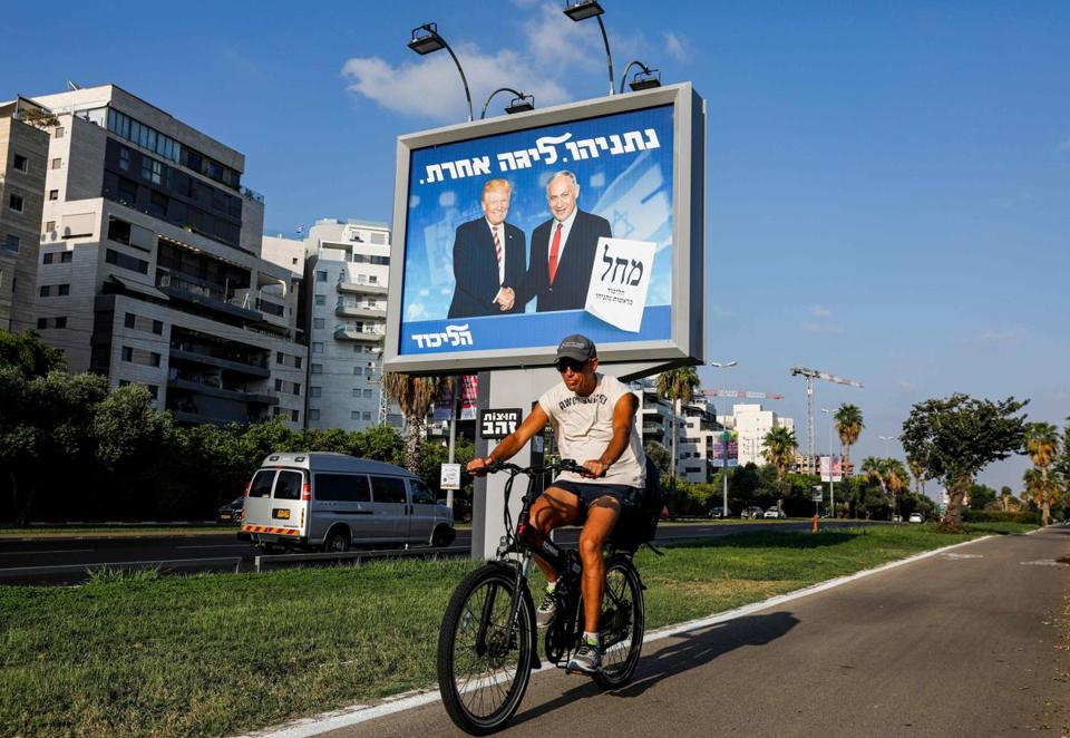 "A man cycles beneath an Israeli electoral billboard for the Likud party showing US President Donald Trump shaking hands with Likud chairman and Prime Minister Benjamin Netanyahu with a caption in Hebrew reading ""Netanyahu, in another league"" in the coastal city of Tel Aviv on September 10, 2019. (Photo by AHMAD GHARABLI / AFP)AHMAD GHARABLI/AFP/Getty Images"