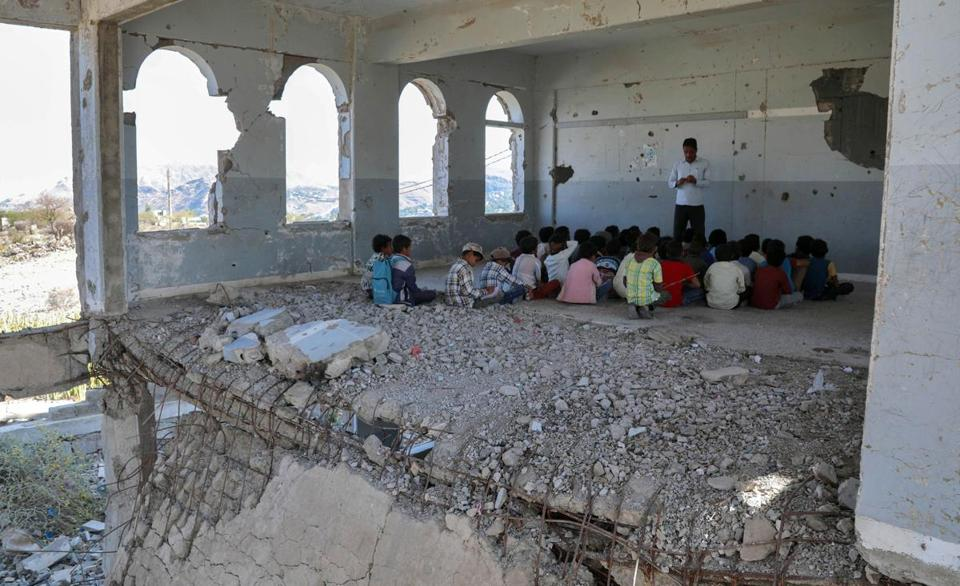 Yemeni children attend the first day of class in a school that was damaged by an air strike during fighting between the Saudi-backed government forces and the Huthis.