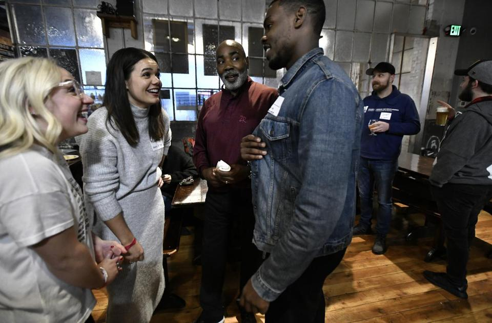 "From left, organizers Claire Wickersham, 28, and Natalie Shellito, 29, talked with off-duty Boston police Officer Frank Williams, 57, and C.J. Louis, 24, at Dorchester Brewing Co. ""People have a negative view toward aging,"" Wickersham said, ""and that's got to change."""