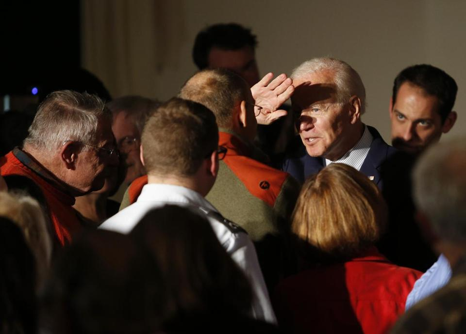 Biden raised his hand to shield his eyes from bright lights in Rochester.
