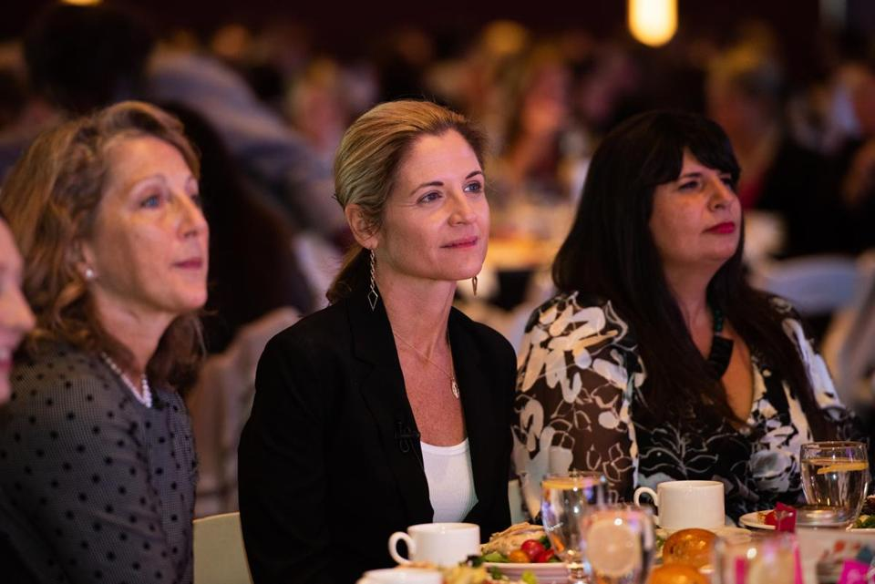 18funnywomen - Featured speaker Glennon Doyle, center, watches videos of RosieÕs Place guestsÕ inspirational stories, flanked by, left, Massachusetts First Lady Lauren Baker, and, right, RosieÕs Place President/Executive Director Leemarie Mosca. (David Fox)