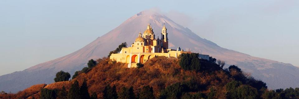 Framed by a volcano, the 16th-century Iglesia  de Nuestra Señora de los Remedios (above) sits atop the Tlachihualtepetl  pyramid 30 miles outside of Puebla.
