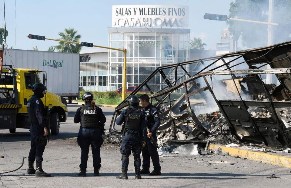 Policemen stand next to a burnt vehicle after heavily armed gunmen waged an all-out battle against Mexican security forces in Culiacán, Sinaloa state, Mexico, on Oct. 18.