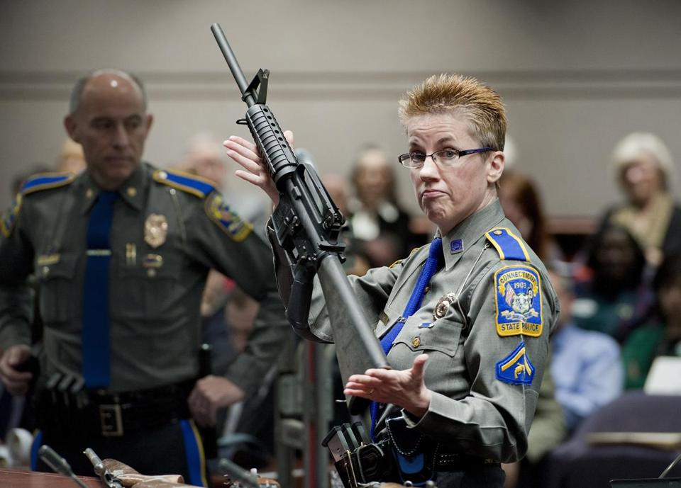 FILE - In this Jan. 28, 2013, file photo, firearms training unit Det. Barbara J. Mattson, of the Connecticut State Police, holds up a Bushmaster AR-15 rifle, the same make and model of gun used by Adam Lanza in the Sandy Hook School shooting, for a demonstration during a hearing of a legislative subcommittee reviewing gun laws, at the Legislative Office Building in Hartford, Conn. Ten states and nearly two dozen members of Congress are joining the National Rifle Association in supporting gun-maker Remington Arms as it fights a Connecticut court ruling involving the Sandy Hook Elementary School shooting. (AP Photo/Jessica Hill, File)