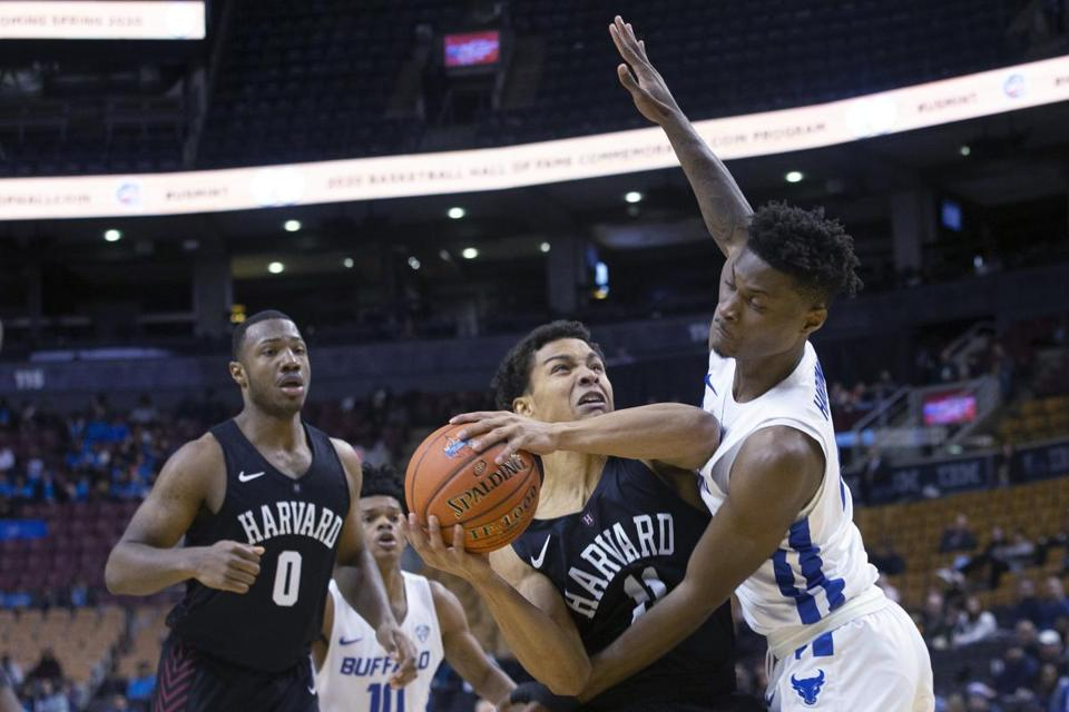 Harvard's Bryce Aiken, center, drives to the net on Buffalo Bulls' LaQuill Hardnett during second half of an NCAA college basketball game in the James Naismith Classic, in Toronto on Saturday, Nov. 16, 2019. (Chris Young/The Canadian Press via AP)