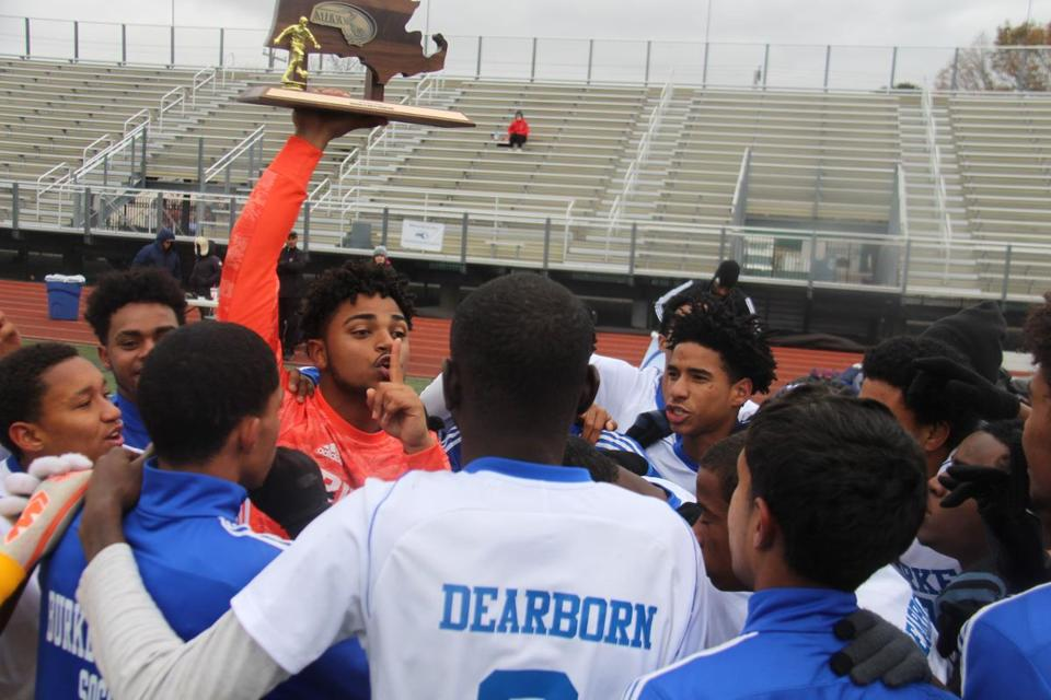 Burke junior keeper Cleidison Lopes, holding the D4 North trophy above his head, presses a finger to his lips to lead his teammates in a chant after defeating Manchester Essex, 4-0, to win the sectional title.