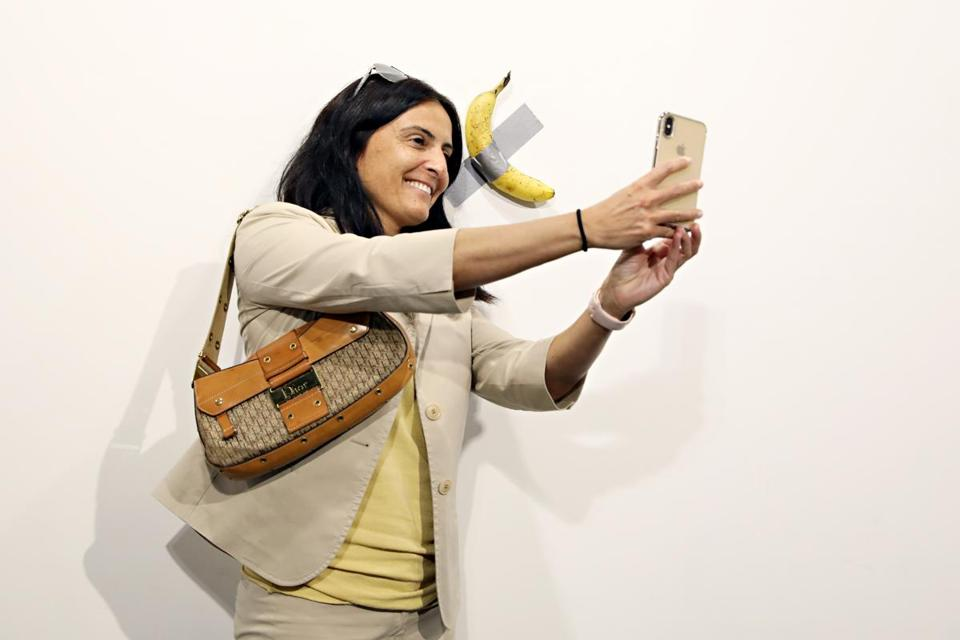 "MIAMI BEACH, FL - DECEMBER 06: People post in front of Maurizio Cattelan's ""Comedian"" presented by Perrotin Gallery and on view at Art Basel Miami 2019 at Miami Beach Convention Center on December 6, 2019 in Miami Beach, Florida. Two of the three editions of the piece, which feature a banana duct-taped to a wall, have reportedly sold for $120,000. (Photo by Cindy Ord/Getty Images)"