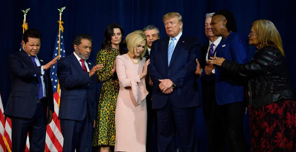 "President Trump (center) stood in a prayer circle with faith leaders during an ""Evangelicals for Trump"" campaign event at the King Jesus International Ministry in Miami last week."